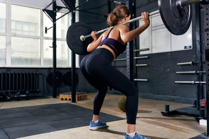 Woman squatting with a barbell at the gym.