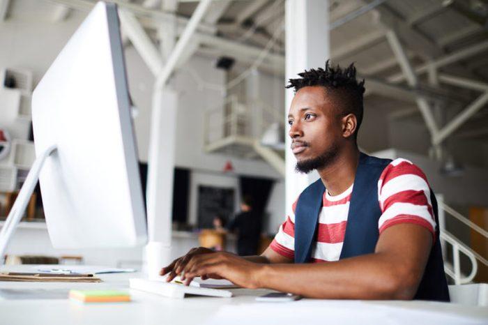 Man sitting at his desk looking at his computer monitor.