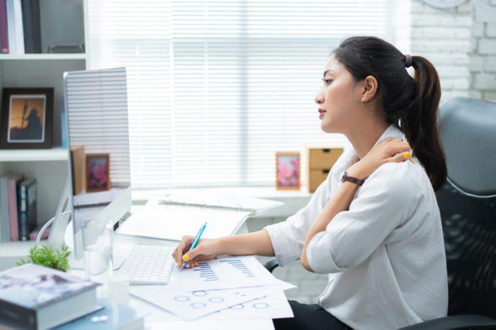 Woman at her desk holding her shoulder.