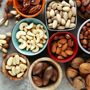 mixed nuts on grey background. Healthy food and snack. Walnut, pecan, almonds, hazelnuts and cashews