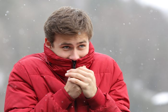 Man shivering in cold winter and rubbing hands while is snowing