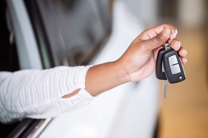 african american woman with her new car showing key