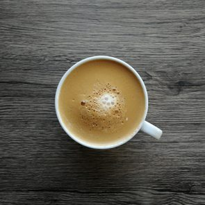 Coffee mocha in a white cup on a black wooden table.