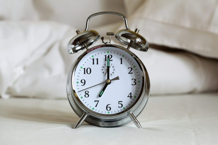 Alarm clock set to 7am ringing on an empty bed