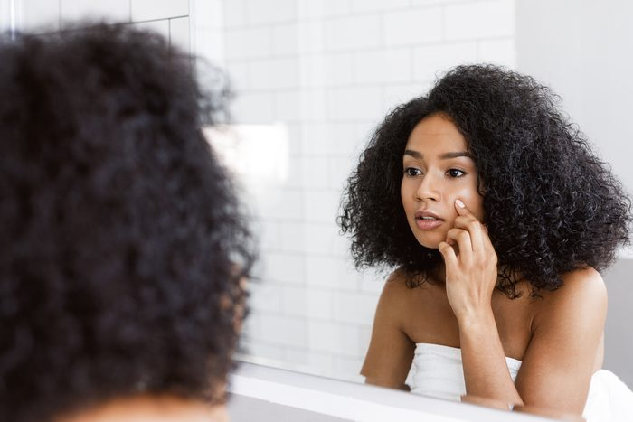 A young woman looking at mirror and examines her skin, touching face with finger