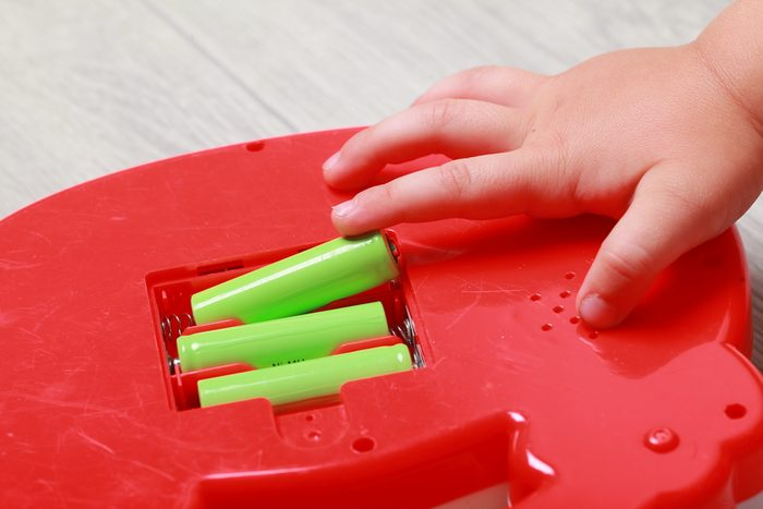 hand the child put the batteries in the red toy