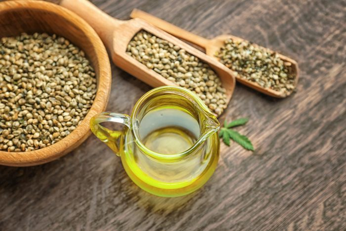 Composition with hemp oil and seeds on wooden background