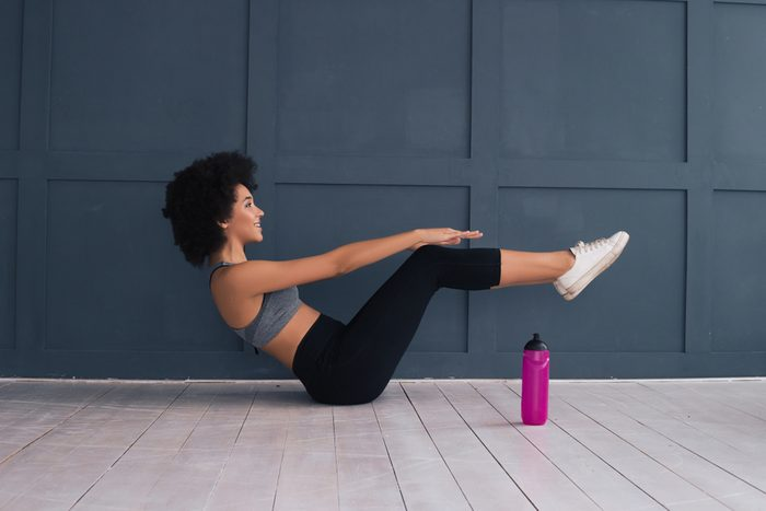Take care of your body and it will take care of you! Beautiful African American young woman doing abdominal crunches indoors.