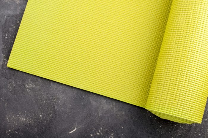 Yoga mat on dark background. Equipment for yoga. Concept healthy lifestyle, sport and diet. Copyspace. Selective focus