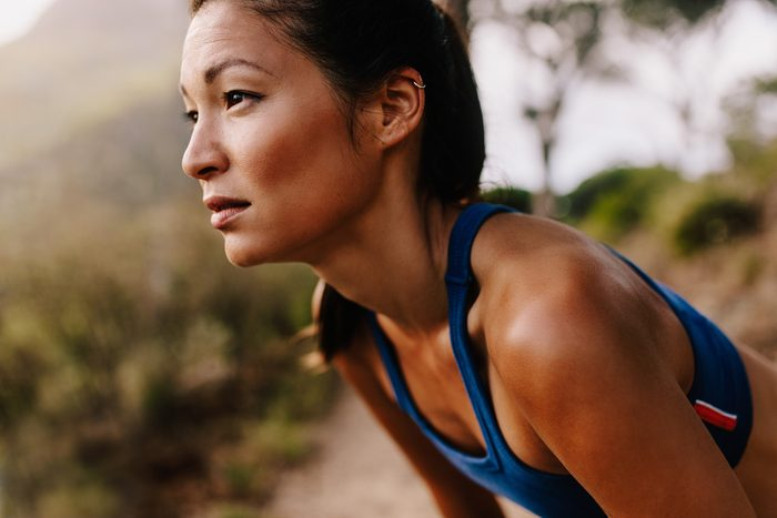 Close up of young asian woman resting after workout and looking away. Female runner in sportswear taking a break.