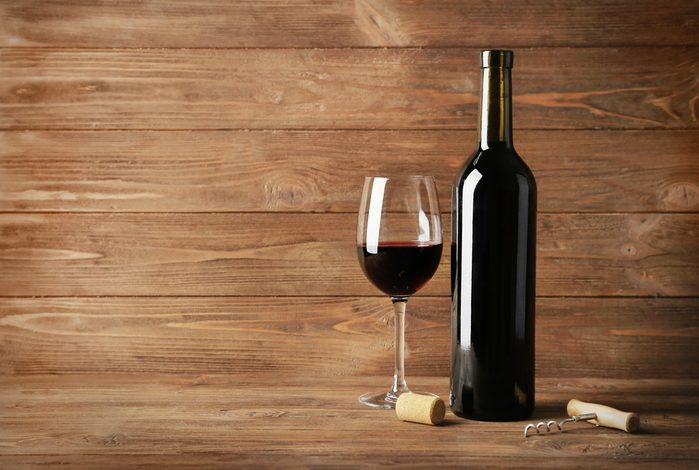 Wine bottle and glass of red wine on wooden background