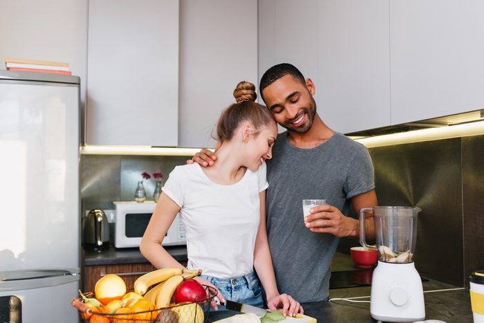 A young couple making breakfast in the kitchen. Men and women in T-shirts embracing each other, cook together, the couple hugging with happy faces and a smile on their faces. family life.