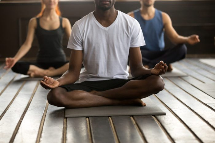 Young black man and a group of sporty people practicing yoga lesson with instructor, sitting in Sukhasana exercise, Easy Seat pose with mudra gesture, working out, indoor close up, studio floor