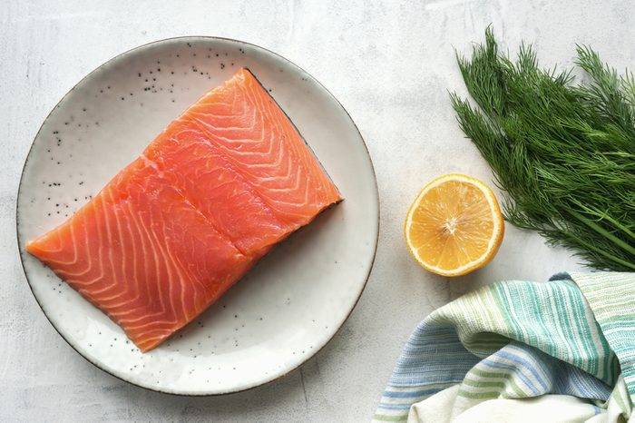 Fresh salmon steak, lemon, black peppercorn and dill on concrete table. Top view. Scandinavian ingredients for cooking. Overhead view.