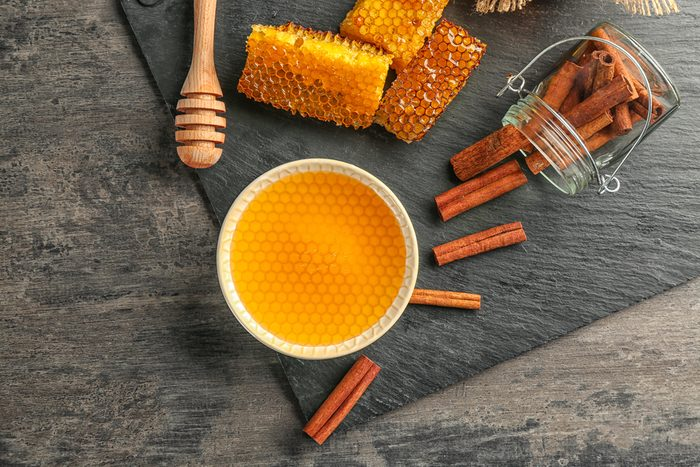 Composition with honey and cinnamon on wooden table