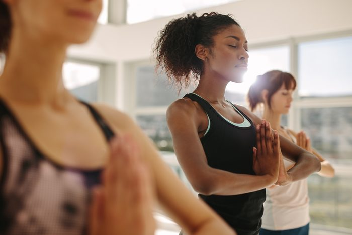Fit young woman practice yoga with friends. Fitness female doing yoga meditation indoors in gym class.