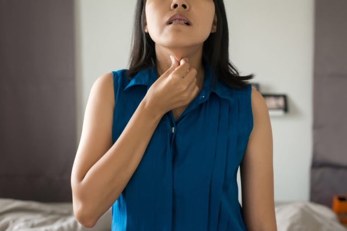 Woman with touching her neck with a sore throat.
