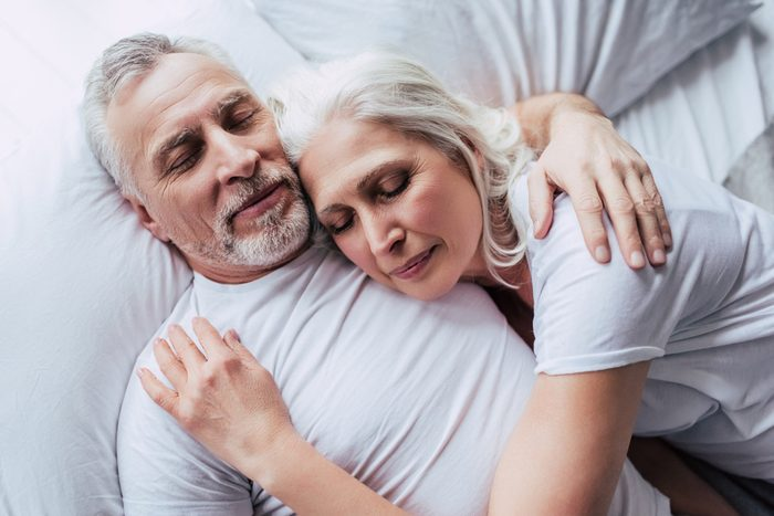 Love lives forever! Senior couple at home. Handsome old man and attractive old woman are enjoying spending time together while lying in bed.