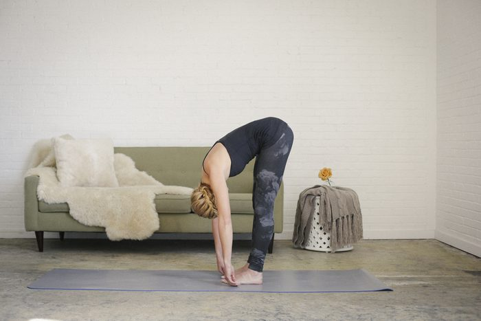 A blonde woman in a black leotard and leggings, standing on a yoga mat in a room, doing yoga, bending down, touching her toes with her hands