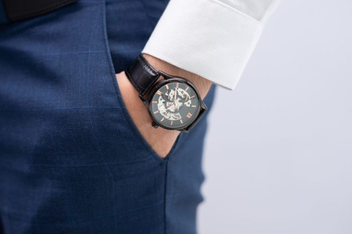 Man's hand in pocket showing wrist watch