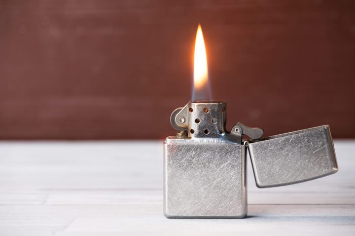 Open cigarette lighter with flame