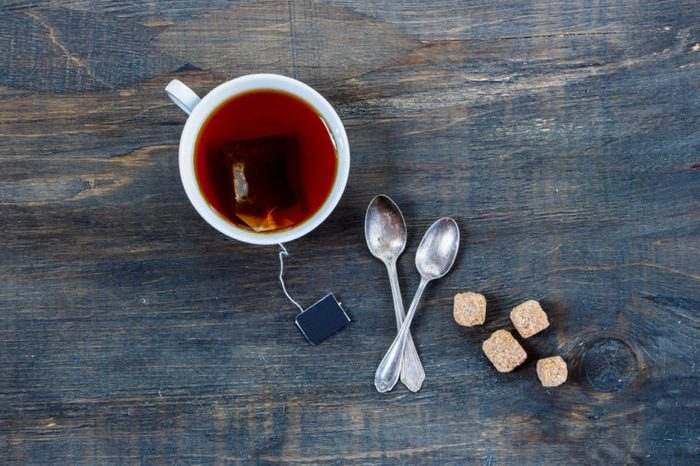Overhead view of cup of tea with two spoons and cubes of brown sugar