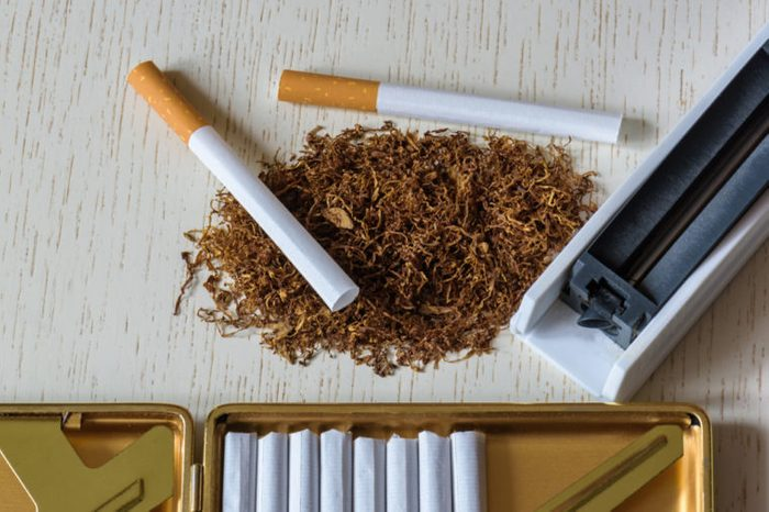 Cigarettes with pile of loose tobacco on a table