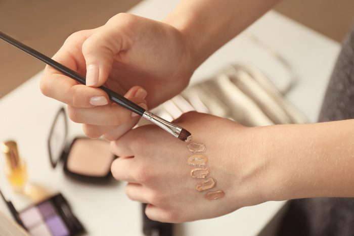 a woman brushing foundation colors onto the back of her hand