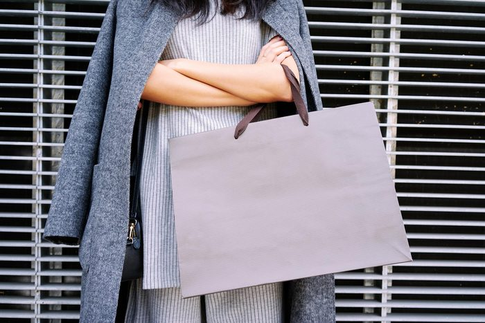 woman with arms crossed holding a shopping bag