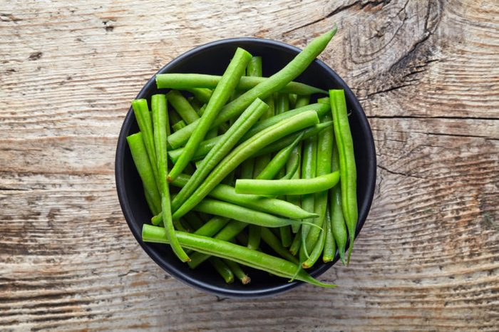 Bowl of green beans on wooden background, top view