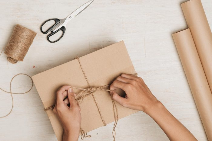 woman tying up a package with string