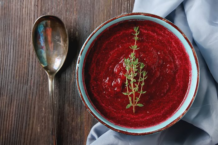 Traditional beetroot soup in a blue plate with Temyan. Dark wood background. Light fabric. free space text. Top view
