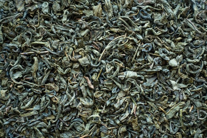 Dry green tea as background or texture top view