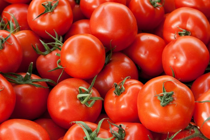 Red ripe tomatoes background with green roots