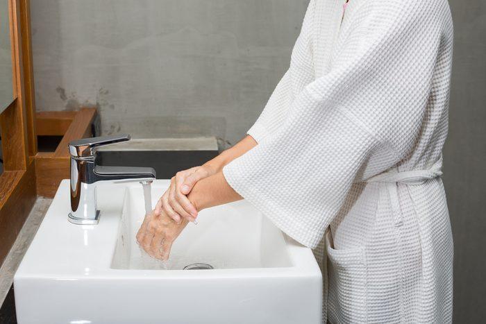 Woman in a bathrobe is washing hands.