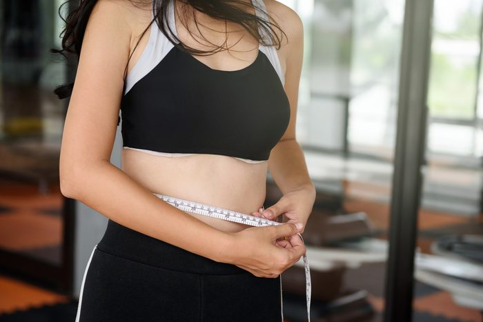 Asian beautiful skinny slim girl, 20-30 years old, measuring her thin waist of 24 inch by tape measure at fitness sport club. Sport and Healthy lifestyle concept