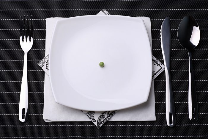 place setting including silverware and white plate filled with One pea