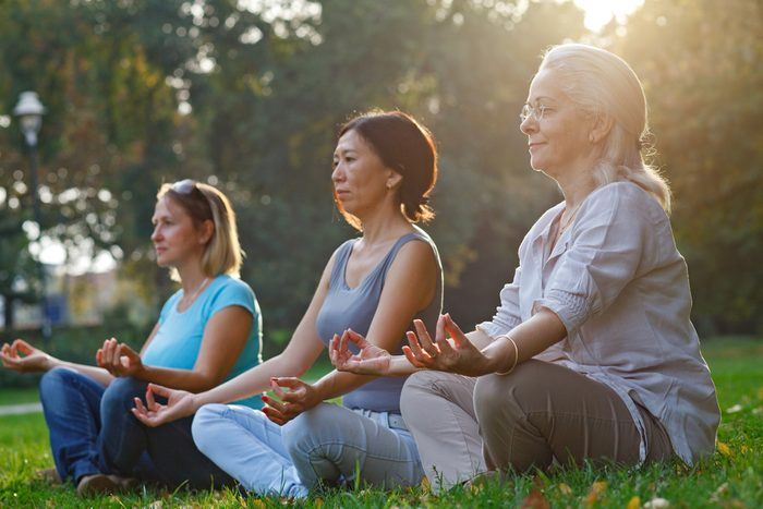 Three ladies meditate while sitting on the grass