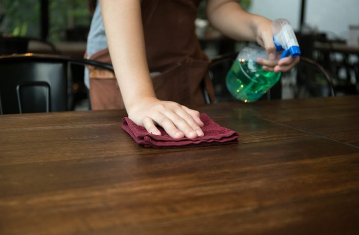 Waitress cleaning the table with spray disinfectant in a restaurant