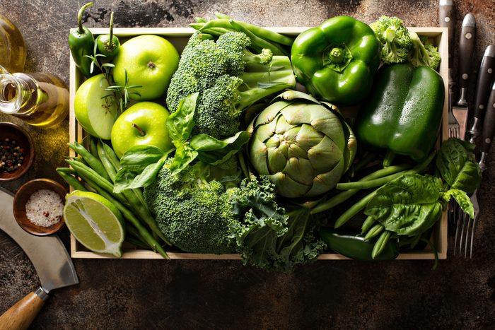 Variety of green vegetables and fruits in a crate on the table