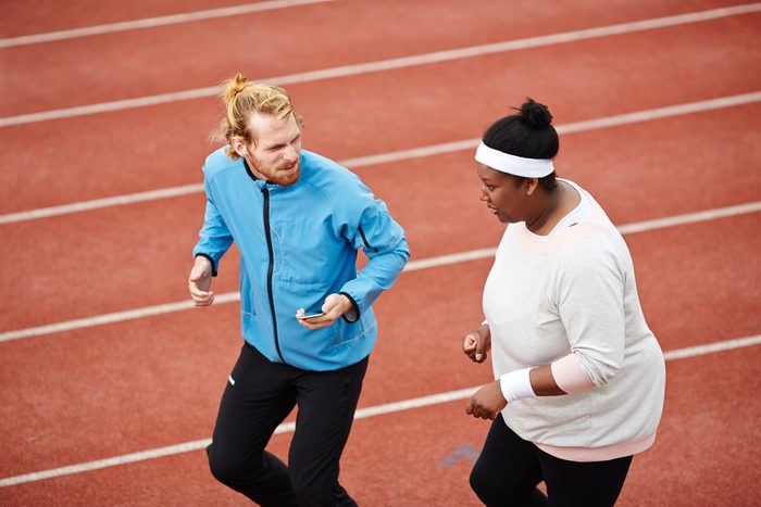 Young instructor and plump female jogging together on stadium racetrack before marathon competition