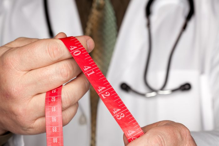Doctor with Stethoscope Holding Red Measuring Tape.