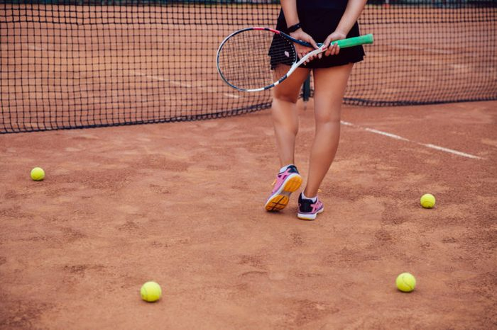 Woman holding a tennis racket on a clay tennis court.