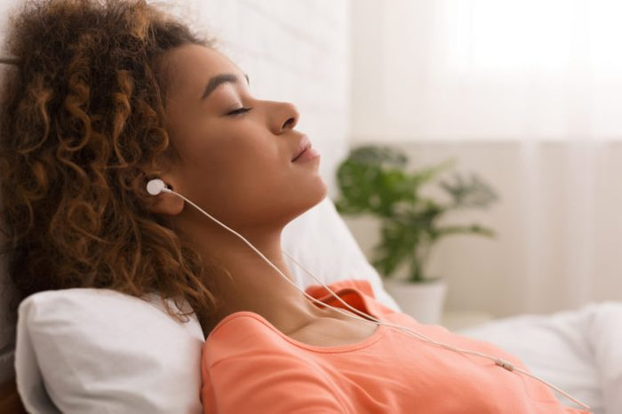 woman listening to calming music in bed