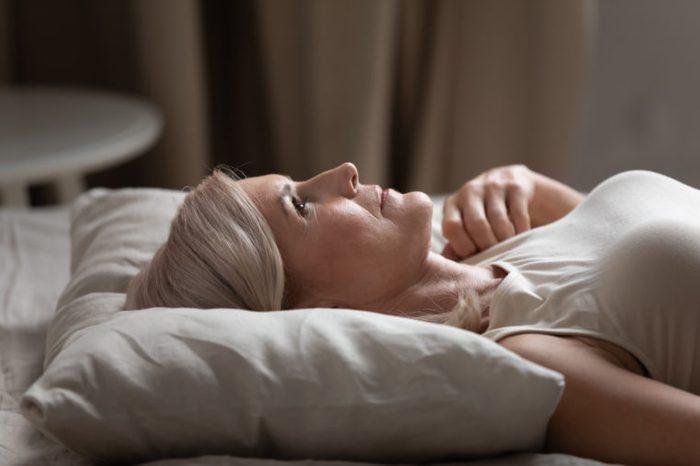 older woman laying awake in bed