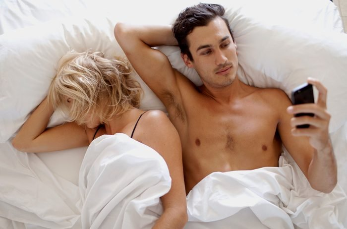 man looking at phone in bed with woman