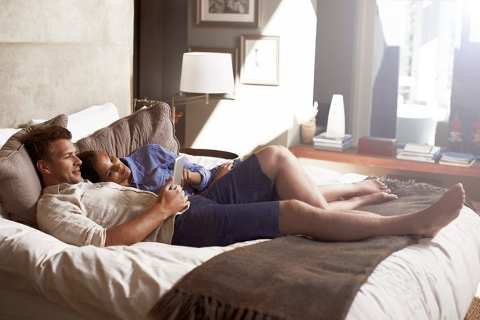 couple lying in bed together using digital tablet