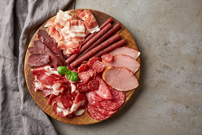 Cold smoked meat plate with prosciutto, salami, bacon, pork chops, cheese and olives on gray stone background. From top view