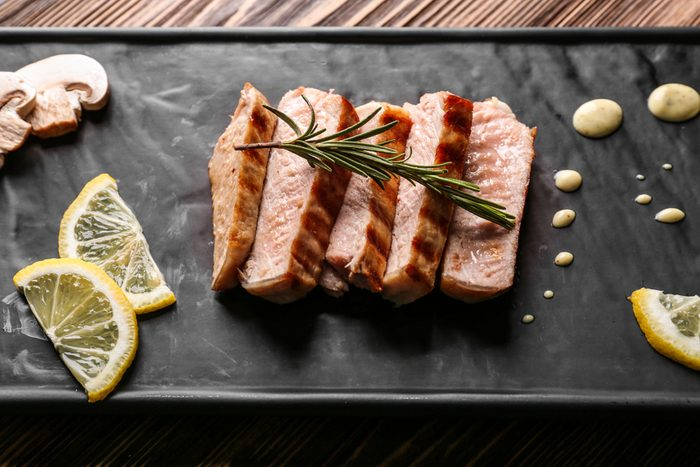 Delicious grilled meat with lemon and sauce on tray