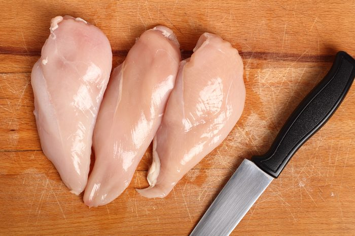 Chicken breast and knife on wooden cutting board. Directly Above.